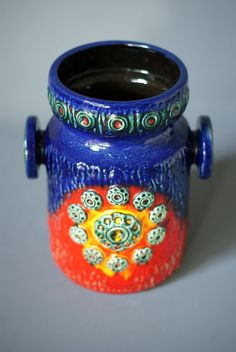 A brightly decorated West German Pottery double-handled vase from the Dümler and Breiden Relief series.  Dümler & Breiden, founded by Peter Dümler & Albert Breiden, commenced pottery production in the 1880s in the German town of Höhr.  Named `Saturn`, the decor is very bright and warm, in colours of blue, red, yellow and green. Stamped into the underside of the vase is the D & B mark, are the identifiers 90 25 and Germany.  DIMENSIONS: Height 25cm (9.8) Diameter opening...