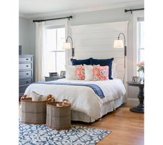Descomplique. Dois cestos grandes resolvem o cantinho ao pé da cama e deixam almofadas e outros itens à mão.