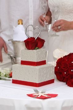 Square 2 tier wedding cake with beautiful scroll work, silver dragees, red ribbon & silver heart cake topper with red roses. <3