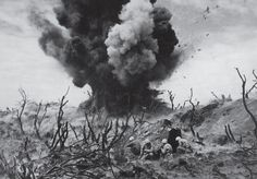 In a picture that captures the violence and sheer destruction inherent in war perhaps more graphically than any other ever published in LIFE, Marines take cover on an Iwo Jima hillside amid the burned-out remains of banyan jungle, as a Japanese bunker is obliterated in March 1945. (W. Eugene Smith—Time & Life Pictures/Getty Images) See more: http://ti.me/Ot3lla