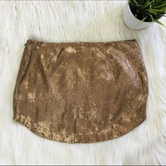 """Copper Sparkly Mini Skirt This is a sequined mini skirt from urban outfitters. Original tag is no longer on it so I don't know the exact size. Please use these measurements against a skirt you already have. It would probably got a xs. 15"""" across the top. 14"""" from top to bottom. Some loose threads which I tried to show in the last two photos. But overall good used condition. Only asking 10 for it! Urban Outfitters Skirts Mini"""