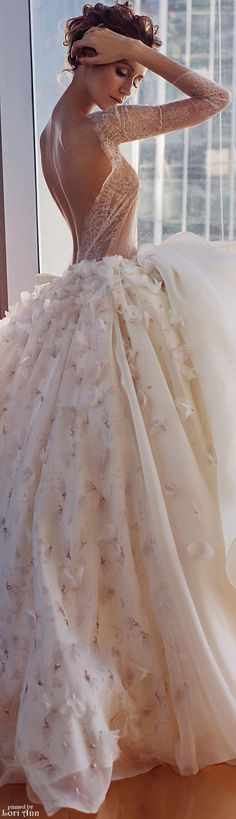 Gorgeous wedding dress with a sheer lace bodice and sleeves and full floral skirt