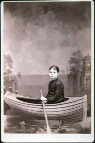 studio portrait of a girl in a boat, ca. 1890