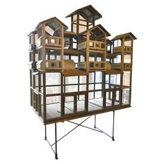 Italy 1900-1920.  Hugh Italian whimsical bird house.Twelve smaller cages,each separated by wooden tray for cleaning or combining. Each smaller cage has two feeding doors that lift for access.The 7 upper cages have tole roofs and 12 tole roofs on sides.  Measurements  height: 7 ft. 2 in.  depth: 41 in.  width/length: 6 ft. 9 in.