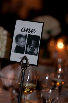 Wedding table numbers using pictures of the bride groom at that age.