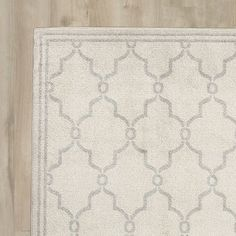 Anchor your aesthetic with this eye-catching rug, featuring a quatrefoil trellis print in neutral tones.