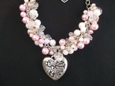 COST: £8.00!    This necklace is made from a selection of pink and ivory fake pearl beads, clear flower shaped beads, white beads, and an engraved metal heart at the bottom.  Total length: 38 cm/15 inches approx.(length does not include extension chain)  Diameter of heart: 3.5cm/1.5 inches approx.