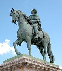 Rytterstatue af Frederik V udenfor Amalienborg. Statuens hoved er rettet mod kirken, og der kan derfor skabes noget religiøst. Værk af Jacques-François-Joseph Saly og blev indviet i 1771