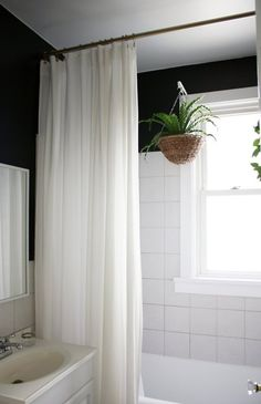 Paint the walls in a small bathroom dark above the tile to make the walls recede. Hang a shower curtain at the ceiling to make the space seem taller.