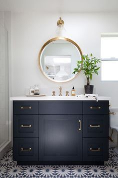 Gorgeous round mirror and navy cabinet