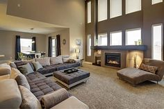 Widhalm Custom Homes Omaha Woodland Model living room family room fire place large modern sectional sofa couch chaise lounge brown grey gray accent wall open floor plan texture carpet glass built in shelf espresso mantle floor to ceiling windows two story vaulted by dona