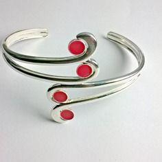 Bracelet rouge corail rigide en métal.