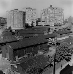 1963 . Kamppi. Malminkadun ja Runeberginkadun välistä aluetta. Kaasulaitoksen kaasukello. Taustalla liikerakennuksia, mm. autotalo eli Veho (Runeberginkatu 3).