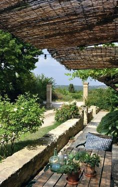 Petite terrasse ombragée en Provence - love the low wall that can be used for seating, the wood plank table, the woven mat sun shade and, of course, THE VIEW!