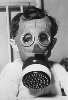 Child wearing a 'Mickey Mouse' gas-mask during the Second World War., Ministry of Information official photographer Old Photos, Vintage Photos, Arte Horror, World War I, Kids Wear, Wwii, Gas Masks, Mickey Mouse, Two By Two