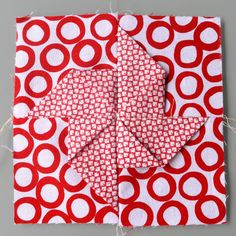 Detail of origami pinwheel Block type:log cabin Block size:11 inches Colour scheme:reds and neutrals Texture/fabric manipulation:fabric folding / fabric origami Quilt size:The finished quilt i…