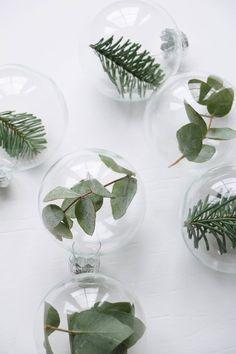 Des boules de Noël transparentes dans lesquelles on aura placé des branches de sapin et d'eucalyptus : la bonne idée pour une décoration de Noël élégante et nature #DIY #deco #noel