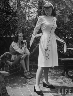 Young girls observing a dress that they have designed, 1944 - Photo by Nina Leen 40s fashion white dress novelty print day wear casual white floral
