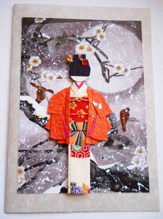 "All-purpose handmade card 44. Hand-folded Japanese paper doll mounted on print of a classic Japanese painting. Materials: Kimono, jacket and obi (yuzen washi); metallic and viscose cords on obi; hair decor (paper strip, bud sticks and Indian ""bindi"")."