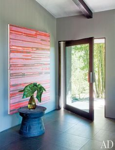 John Legend's Hollywood Hills Home - A painting by Mark Harrington and a Pottery Barn rain-drum table accent the entrance hall.