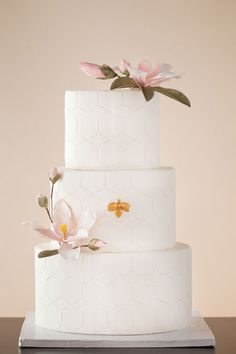 Brides: Honeycomb Wedding Cake. Created by the Wild Orchid Baking Company in New Hampshire, the design features a subtle honeycomb pattern pressed into smooth fondant. The middle tier is embellished with a fondant honey bee that's been brushed with edible gold, and two gumpaste magnolias—a honey bee's favorite bloom during the spring and summer months—adorn the top and bottom tiers.