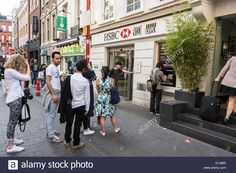 Download this stock image: People queuing outside the HSBC cash point machine on…