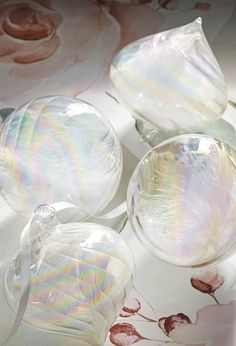 A white feather is swathed in mouth-blown glass, producing a soft iridescent effect that will bring unexpected delicacy and depth to any greenery. This set includes two ball shapes and two onion shapes, each with a ribbon for hanging.