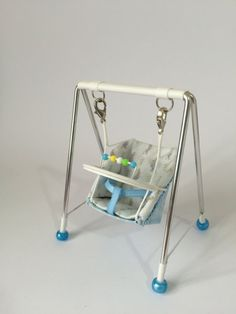 Tiny swing for your dollshouse baby, 1/12th scale, this one is made in blue fabric for the back of the swing, and cute rabbit fabric for the seat, Removable play tray Other items to match are available. This item is not sent signed for delivery, I always keep proof of posting All my