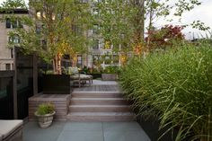 Soft uplights draw the eye to tree trunks on the deck of a rooftop garden in Soho, New York by Robin Key Landscape Architecture