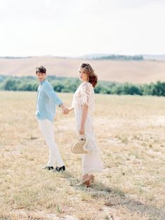 Italian Elopement in the Rolling Hills of Tuscany | Wedding editorial in Tuscany Italy, romantic couple session in Siena, engagement shooting inspiration, white top with floral details and white pants, small wicker bag, blue shirt and white pants, elopement photoshoot in Tuscany countryside