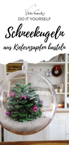 Zapfen sehen wie kleine Weihnachtsbäume aus! Perfekt also, um damit Schneekugeln zu basteln. Dieses DIY-Projekt gelingt wunderbar mit Kindern. Am Blog habe ich Dir zusammengeschrieben, welche Materialien Du brauchst. Viel Spaß beim Basteln in der Adventszeit. #diy #bastelnmitkinder #vlikeveronika #weihnachten #geschenkideen