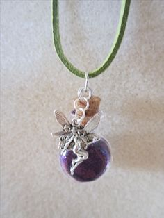 "This super cute Fairy Necklace features Fairy Dust inside of a Miniature Glass Bottle, with a Fairy charm hand strung on a light green Suede leather cord necklace.  The mini bottle is filled with a sparkly purple fairy dust ( Glitter ) Perfect for anyone who is looking for Fairy Jewelry or a Fairy gift.    This necklace is handcrafted and originally designed by The Charmed Crystal L.L.C.   The necklace measures 20"" inches  Pendant measures 1 1/2"" inches long."