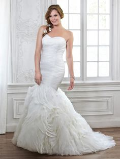 Primrose plus size wedding dress by Maggie Sottero |   Understated, yet rich in design, this tulle and Chic Organza fit and flare features a slimming ruched bodice, with a textured swirling rosette skirt. Finished with strapless, sweetheart neckline and signature corset back closure.