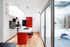 Kitchen White and Red Layers and Colours Defining The Stacked House in Montreal, Canada