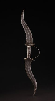 "Indian haladie (double bladed dagger) from the Rajput warriors of India. All steel forged construction, including the handle, with two double edged blades and a knuckle guard. The knuckle guard would have had a third small straight blade sticking out, but it is missing with only an attachment hole remaining. The blades are pitted from old rust, but they are now cleaned of the rust and oxidized dark. 26"" Overall with two 10 1/2"" Blades. 19th century or earlier."