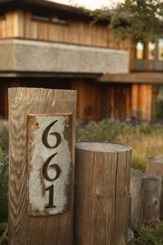 house number sign - love the rustic sign on a post, with another, andfern/shrubs around it on corner of property.