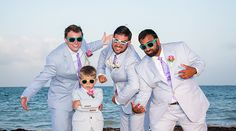 Groom, groomsmen and ring bearer strike a pose on the beach in light blue suits and wayfarer sunglasses | Palace Resorts Weddings ®