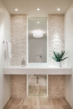 Project by 2id interiors - South Beach Amazing powder room. Simply elegant. Mirror, stone walls, LED lighting, Travertine Floor.