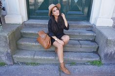 brown boots hat bag, stairs pose, black top and shorts,