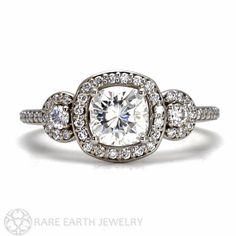A stunning Moissanite and diamond 3 stone engagement ring in your choice of 14K or 18K White, Yellow or Rose Gold. The center stone is a lovely cushion