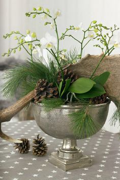 winter centerpiece idea - Silver urn filled with antler, pine cones, evergreen clippings and white floral branches.
