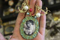 Here is an awesome necklace made with a handmade glass cameo featuring a Victorian tattooed lady! The frame is painted with gold accents, and the pendant hangs on vintage gold tone chain. I added beads and two cute acrylic gold mirror anchor charms!  http://cristinabeller.storenvy.com