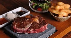 Don't these steaks look delicious? Tuck into exotic meats served on searing hot volcanic stone platters at Steakhouse, Watford Steakhouse London, Wine House, Volcanic Rock, Steak Recipes, Charcuterie, Healthy Cooking, Grilling, Chips, Meals