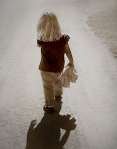 Invisible girl portrait of a child alone walking down an empty road sepia gray tan dark brown, abandoned, sad, lonely