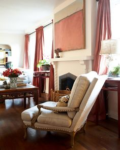 A linen-upholstered armchair with nailhead trim is quietly sophisticated. - Traditional Home ® / Photo: Colleen Duffley / Design: Megan Rice Yager