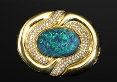Very Fine Black Opal, Diamond and Yellow Gold Pendant/Brooch  Lightning Ridge, New South Wales, Australia   Centering on a fine black opal from the most prestigious region of Australia, this sizable oval cabochon weighs approximately 20.0 carats. A five out of five in vivid play-of-color in a blue-green flame pattern, bezel-set in a substantial 18K yellow gold mount with significant heft (weighing approximately 54.4 grams), pave-set with approximately 3.02 carats of brilliant-cut diamonds