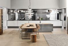 idée déco cuisine moderne en blanc et inox aménagée avec un îlot central en inox et un coin repas en bois