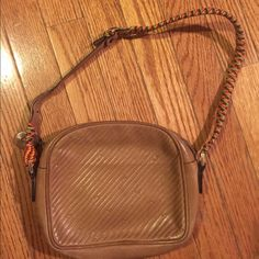 Vintage Lancel Paris Purse This cute bag is a vintage piece by Lancel. It is completely tan, embossed Lancel 'L' logo all over and has a pretty multi-color braided strap. Excellent pre-owned condition. Lancel Bags