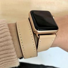 Blush Rose Double Wrap Apple Watch Leather Band by Juxli Home.  Handmade, stylish leather strap with rose gold hardware on a 40mm Apple watch on a canvas with a black and gray painting.