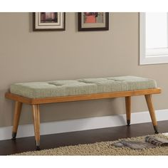 Modern meets retro with this stylish bench. Featuring sleek tapered legs and wooden frame in a rich honey wood finish this mid-century mod bench is complete with a cool aqua blue, reversible button tufted cushion.